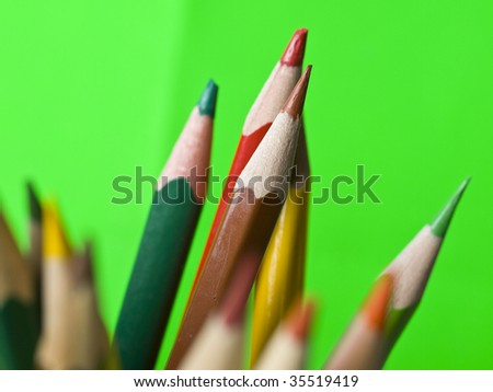 colorful pencils on green background