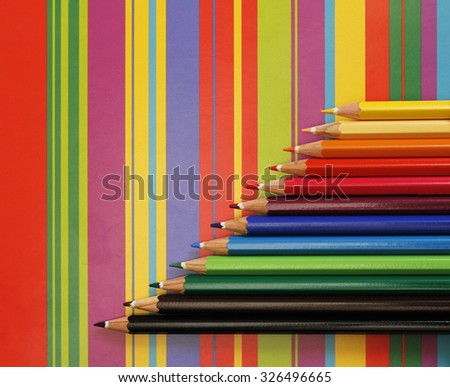 Colorful pencils on striped paper creative design artwork