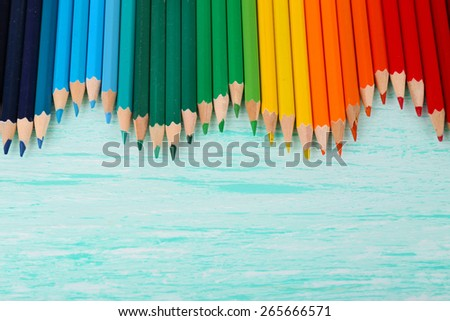 Colorful pencils on wooden table - stock photo