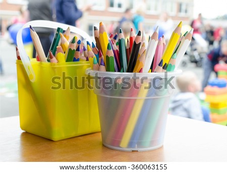 Colorful pencils or crayons in plastic containers on table outside on a school yard