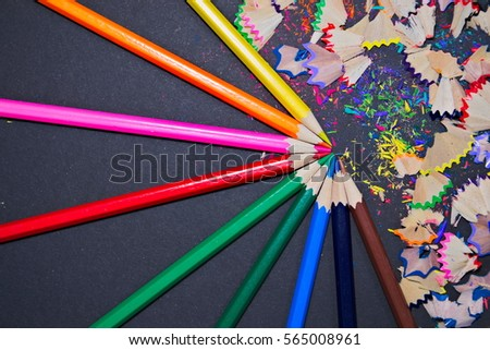 Colorful pencils with colorful shavings on a black background