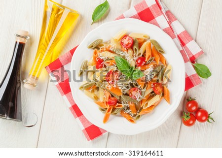 Colorful penne pasta with tomatoes and basil on wooden table. Top view - stock photo