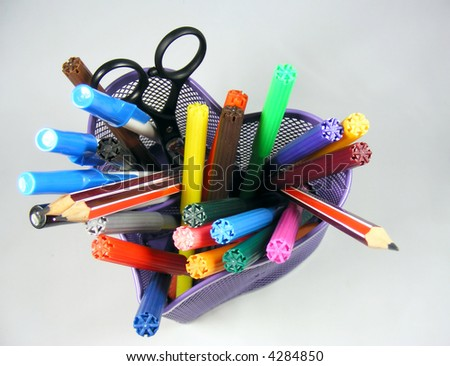 Colorful pens and pencils in a heart shaped container