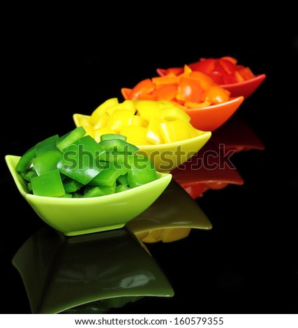 Colorful peppers diced, in bowls on black background. - stock photo