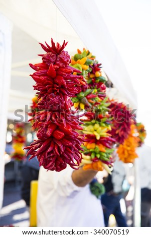 Colorful peppers strung and hanging in market. - stock photo