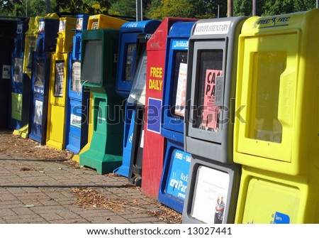 Colorful periodical vending machines along a town sidewalk. - stock photo