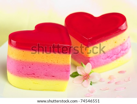Colorful Peruvian heart-shaped jelly-pudding cakes called Torta Helada with a peach blossom on the plate (Selective Focus, Focus on the three upper lines on the front of the left cake) - stock photo