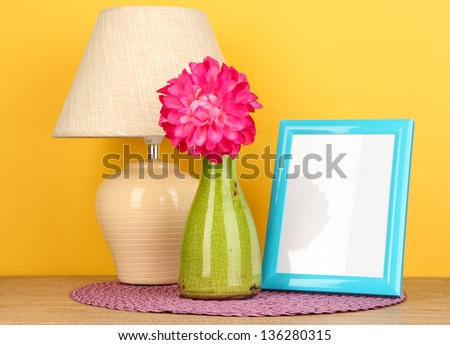 Colorful photo frame, lamp and flowers on wooden table on yellow background - stock photo