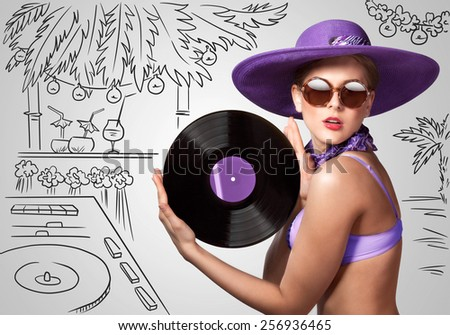 Colorful photo of a beautiful deejay in bikini holding a retro vinyl record in her hands on sketchy background of a DJ mixer and exotic landscape. - stock photo