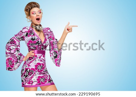 Colorful photo of an amazed fashionable hippie homemaker with metal vintage music headphones around her neck, pointing aside with her finger on blue background. - stock photo