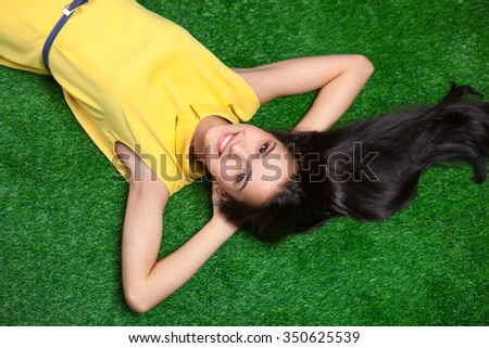Colorful photo of beautiful girl lying on green grass. Young brunette cheerfully smiling and looking at camera - stock photo