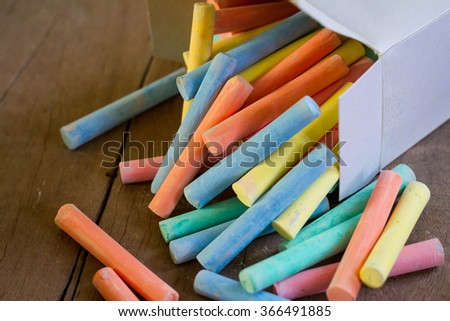 colorful pieces of chalk.on wood  background - stock photo