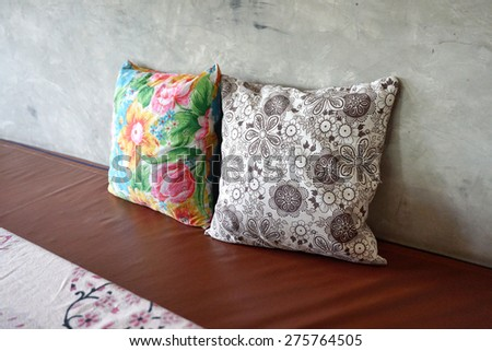 Colorful 2 pieces of flower pattern throw cushion on brown seating and concrete wall background - stock photo