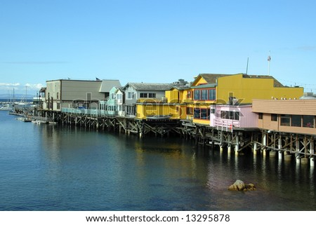 Colorful pier at Monterey, California, with bright blue sky and water - stock photo