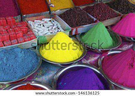 Colorful piles of Indian bindi powder dye at outdoor market in India blue, yellow, green, pink, and purple