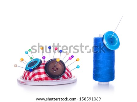 Colorful pillow for needles with blue bobbin, needle and button, isolated - stock photo