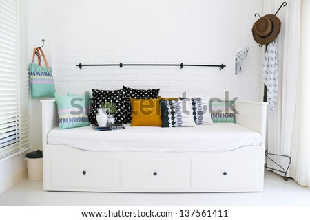 Colorful pillows on a sofa with white brick wall in background - stock photo