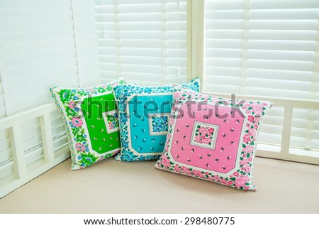 Colorful pillows on a sofa with white window background