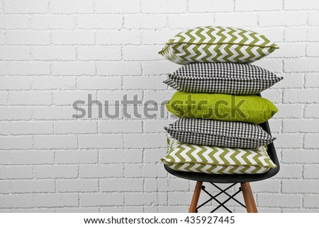 Colorful pillows on chair, on white bricks wall background - stock photo