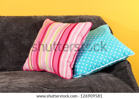 Colorful pillows on couch on yellow background - stock photo