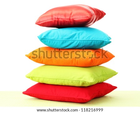 Colorful pillows on table isolated on white - stock photo