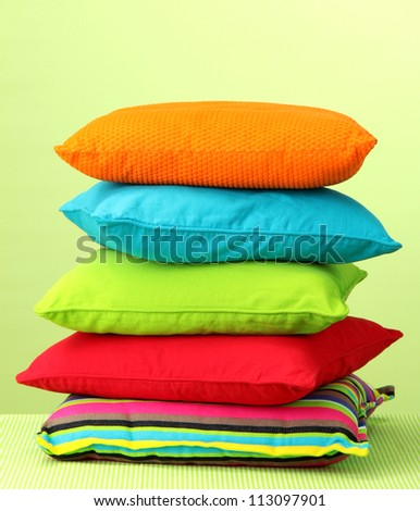 Colorful pillows on yellow background - stock photo