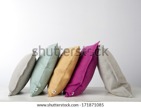 Colorful pillows row isolated on white - stock photo