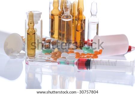 colorful pills, ampules, syringe on white background - stock photo
