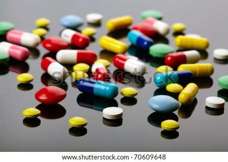 Colorful pills over dark background - stock photo