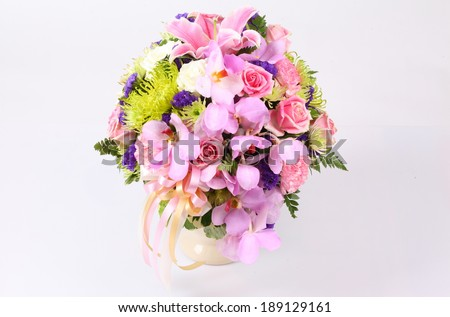 Colorful pink flower arrangement centerpiece with roses, lily, carnations, isolated on white.