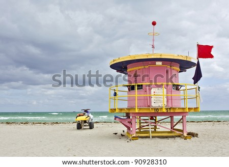 Colorful pink lifeguard house i a typical Art Deco style and a beach rescue car in Miami Beach, Florida with cloudy sky and ocean in the background.