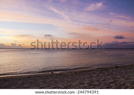 Colorful pink, purple and orange tropical sunset or sunrise reflected in the water over a calm ocean with a deserted idyllic beach in the foreground - stock photo