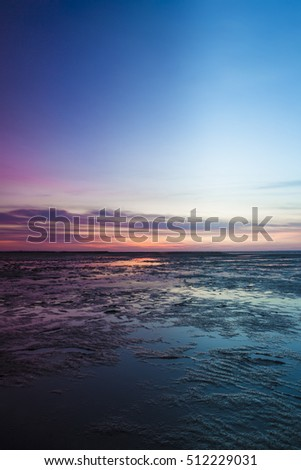 Colorful pink sunset over the North Sea with a calm blue ocean and reflection on the surface of the water