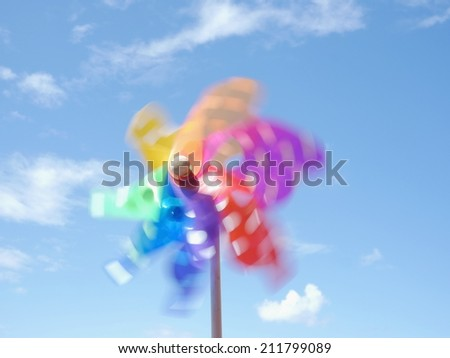 Colorful pinwheel against blue  sky with clouds - stock photo