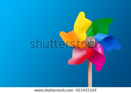 Colorful pinwheel isolated on the blue background with copy space - stock photo