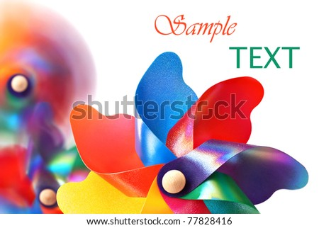 Colorful pinwheel with spinning pinwheels in soft focus in background.  Macro on white background with copy space. - stock photo
