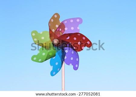 Colorful pinwheels on blue sky - stock photo