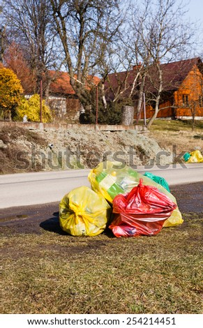 Colorful plastic bags by street in small polish country where environmental responsibility is growing - stock photo