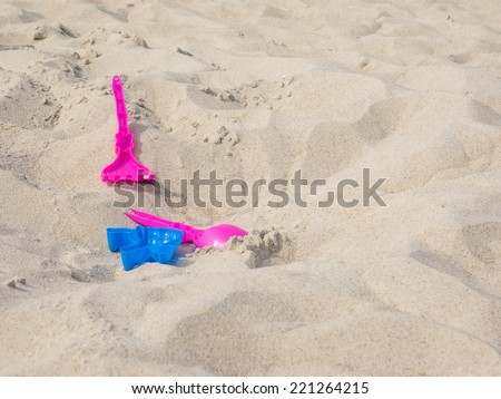 Colorful plastic beach toys on sand . - stock photo