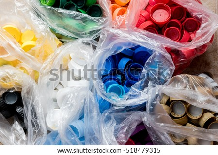 Colorful plastic bottle caps arranged by colors in plastic bags, ready for recycling