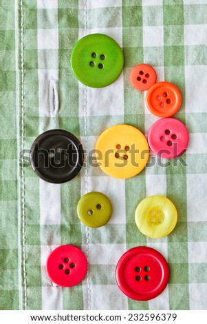 Colorful plastic buttons on a checked shirt as a background image - stock photo
