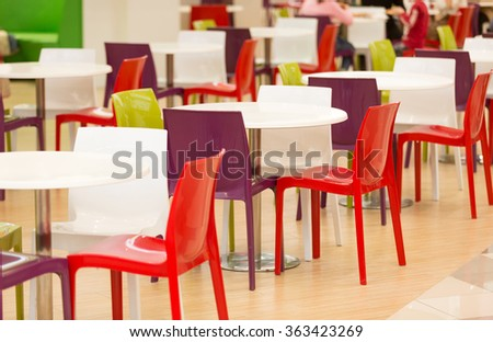 Colorful plastic chairs and tables in big canteen - stock photo