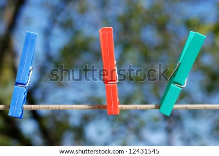 colorful plastic clothes pins on an outdoor laundry line - stock photo