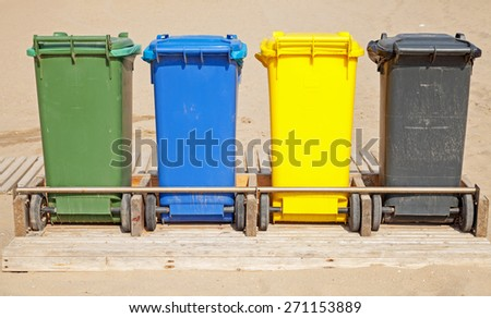 Colorful plastic containers in a row for separate garbage collection, front view - stock photo