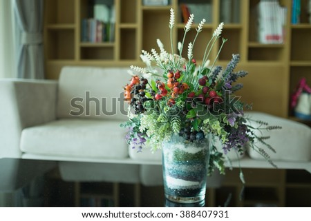 Colorful plastic flowers in glass vase on marble table and cream sofa and wooden cupboard in tidy living room/Colorful plastic flower - stock photo