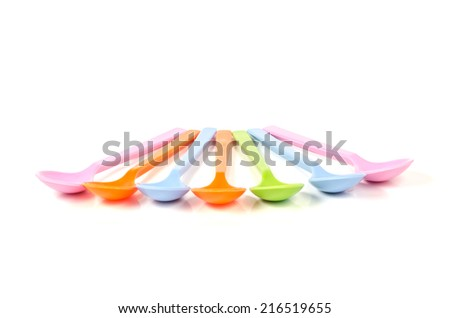 Colorful plastic ice cream spoons on a white background. - stock photo