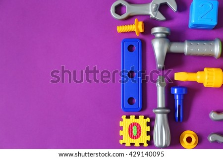 Colorful plastic kids toys on purple background - stock photo