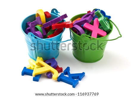 Colorful plastic  letters in small buckets isolated on white background - stock photo
