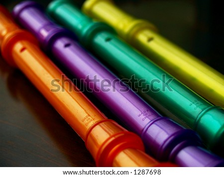 Colorful plastic musical instruments in shallow and soft focus, in orange, purple, green, and yellow on a deep brown background. - stock photo