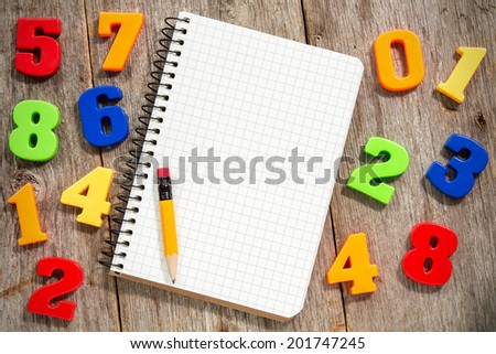 Colorful plastic numbers and empty notebook with pencil - stock photo